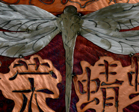 Body of dragonfly flanked by bright characters.