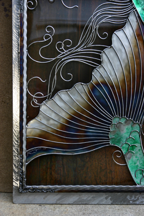 A look at a portion of the fin and hair against the marbled patina metal.
